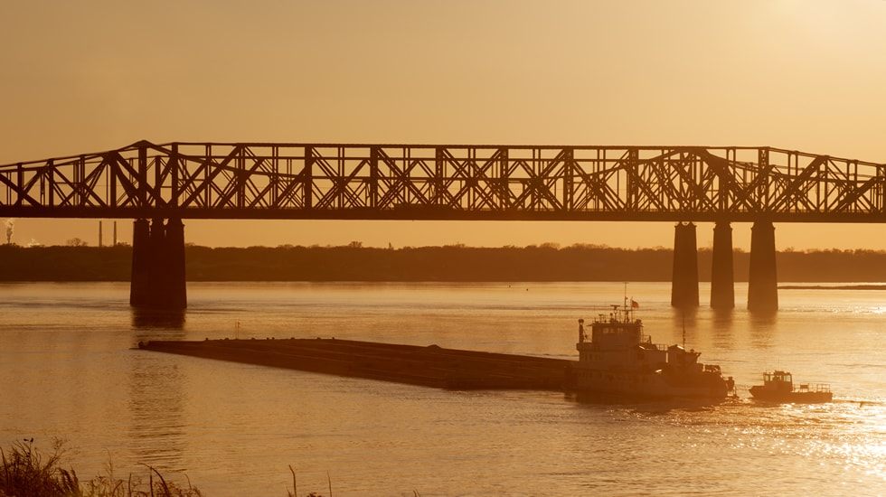 A barge transports product for IOC on a waterway like the Houston Ship Channel.